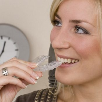 A woman with blonde hair holding an Invisalign aligner in front of her mouth