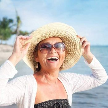 Smiling, happy woman on the beach wearing a hat and sunglasses