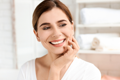 A middle aged woman with her hand on her face and smiling